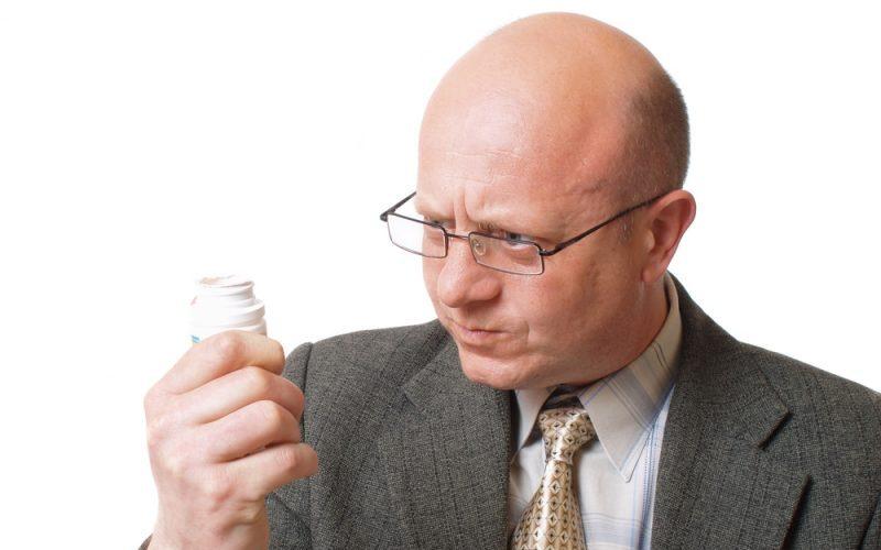 taking-pills-for-miracle-hair-loss-cure-myth-bald-man-vitamins-solution